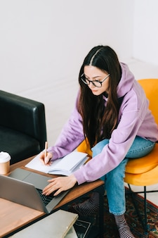 Estudiante universitario de mujer joven caucásica enfocada en anteojos estudiando con computadora portátil, preparándose a distancia para el examen de prueba, escribiendo un ensayo haciendo la tarea en casa, concepto de educación a distancia