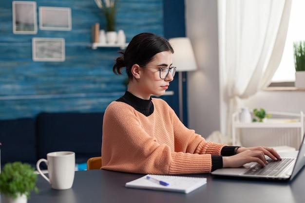 Estudiante universitario navegando publicidad de marketing para la tarea escolar escribiendo información en el teclado usando una computadora portátil. mujer mirando la plataforma universitaria de e-learning mientras está sentado en un escritorio