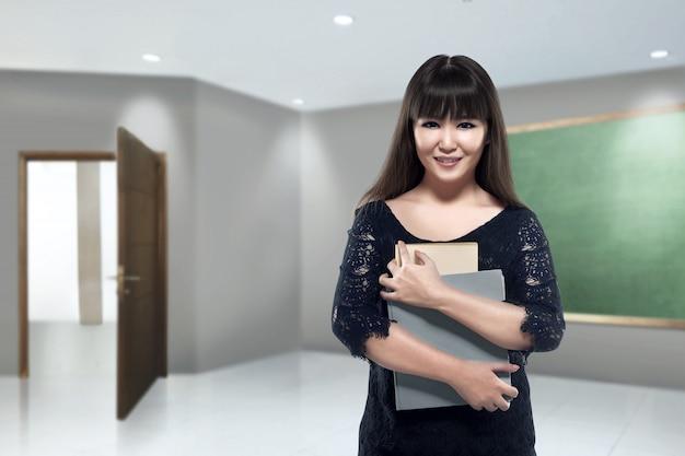 Estudiante universitario de sexo femenino asiático sonriente que sostiene los libros