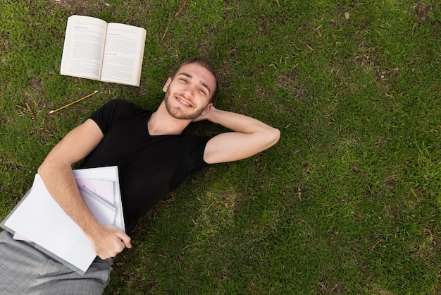 Estudiante universitario tomando un descanso en el césped