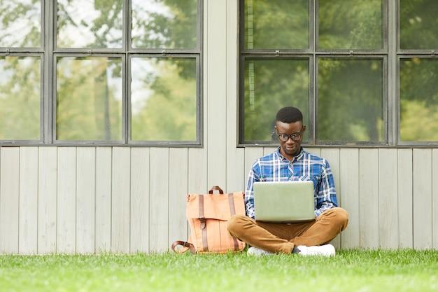 Estudiante universitario usando la computadora portátil al aire libre