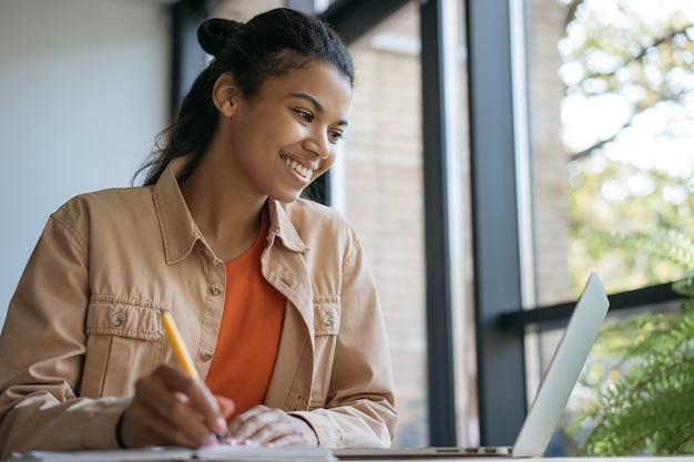 Estudiante universitario usando laptop, estudiando, tomando notas, aprendiendo en línea. sonriente mujer de negocios que trabaja en la oficina