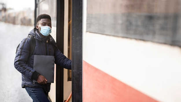 Estudiante varón con máscara sosteniendo libros en la parada de tranvía