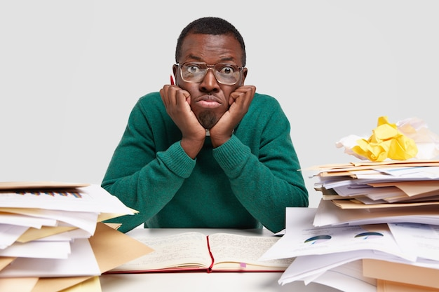 Estudiante varón negro cansado confundido mantiene las manos debajo de la barbilla, usa gafas y un jersey verde, mira con desconcierto