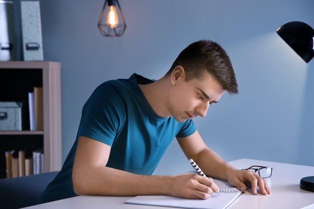 Estudiante varón preparándose para el examen en la mesa en el interior
