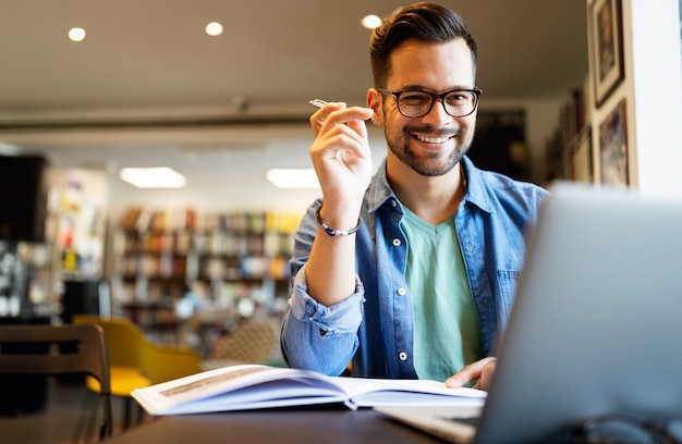 Estudiante varón sonriente trabajando y estudiando en una biblioteca