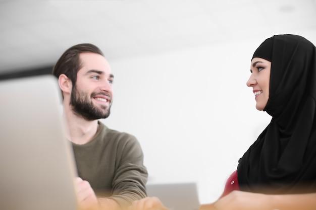 Estudiante varón y su compañero musulmán con laptop en biblioteca