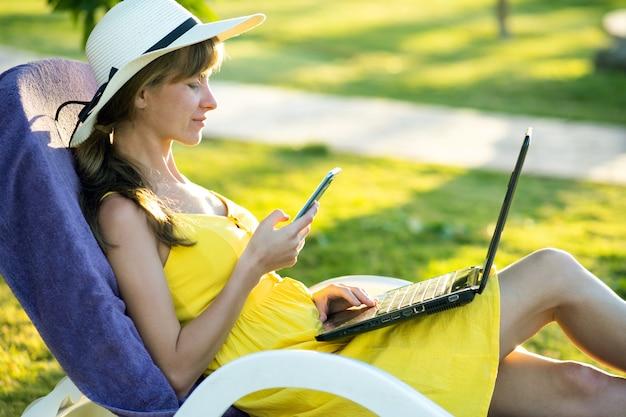 Estudiante en vestido de verano amarillo descansando sobre césped verde en el parque de verano estudiando en computadora portátil mensajes de texto en el teléfono celular móvil.