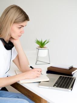 Estudiante de vista lateral en su computadora portátil y planta suculenta
