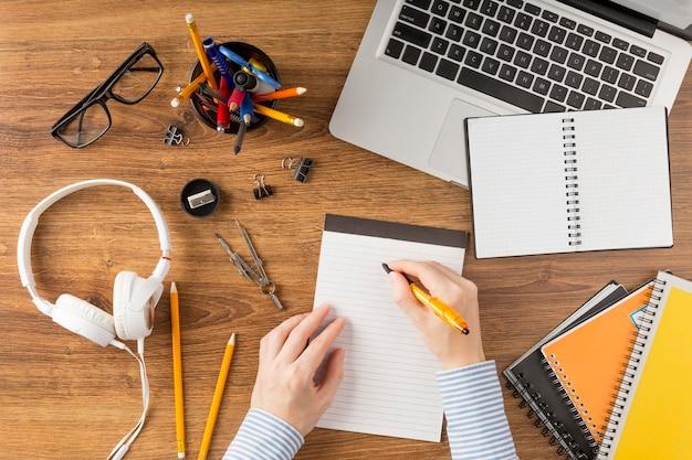 Estudiante de vista superior escribiendo en el bloc de notas