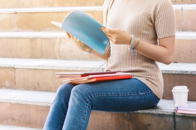 Los estudiantes del adolescente de la mujer joven con los libros se sientan en la escalera