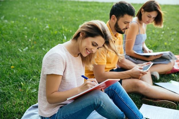 Los estudiantes adolescentes en atuendos casuales con cuadernos están estudiando al aire libre