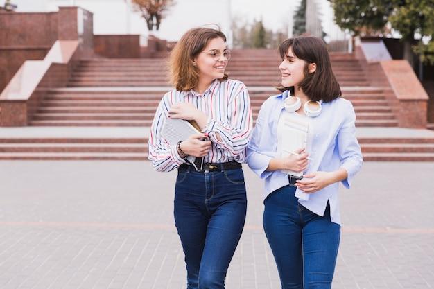 Estudiantes adolescentes en camisas ligeras caminando con libros.