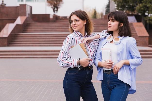 Estudiantes adolescentes en camisas ligeras de pie con libros.