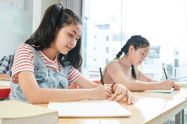 Estudiantes adolescentes concentrados escribiendo en cuadernos cuando asisten a clases en la escuela