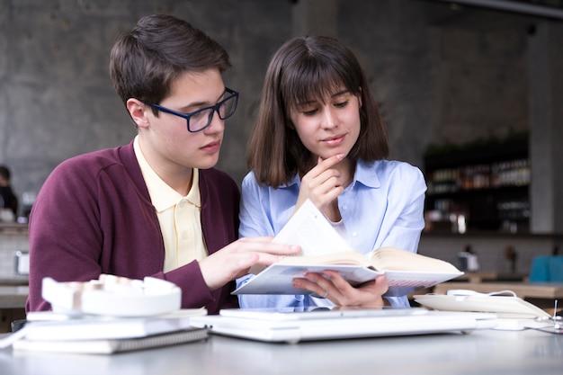 Estudiantes adolescentes estudiando con libro abierto en mesa