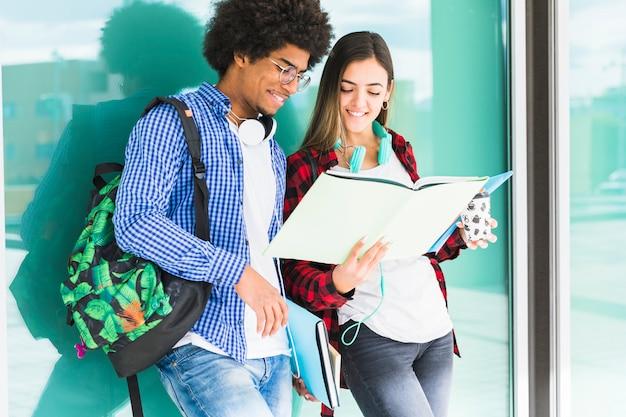 Estudiantes adolescentes con libros y sus bolsas de pie contra el vidrio mirando el libro