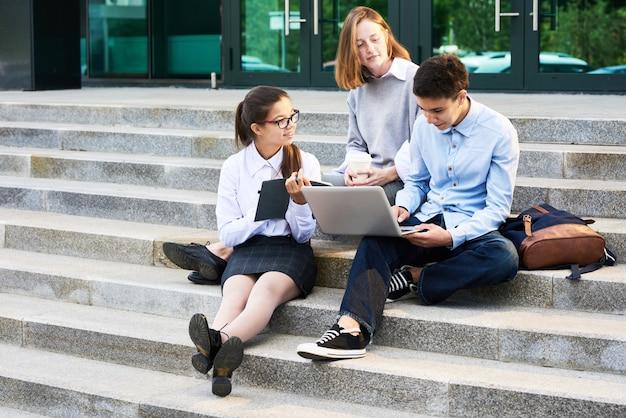 Estudiantes adolescentes trabajando en proyecto escolar