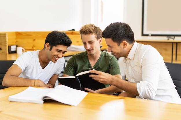 Estudiantes adultos alegres que se divierten en el aula