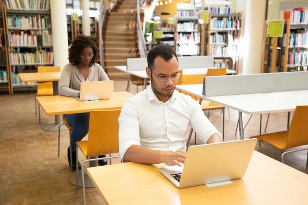 Estudiantes adultos enfocados que toman exámenes en línea