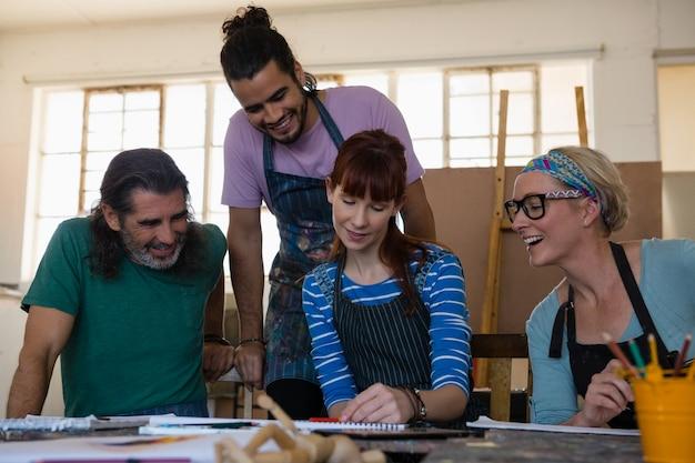Estudiantes adultos mirando a una mujer dibujando sobre papel