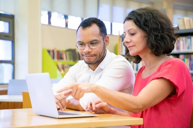 Estudiantes adultos positivos haciendo investigación académica.