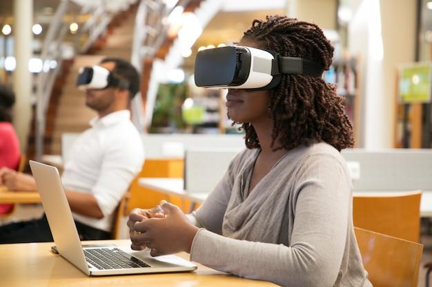 Estudiantes adultos que usan simuladores de realidad virtual para trabajar en proyectos