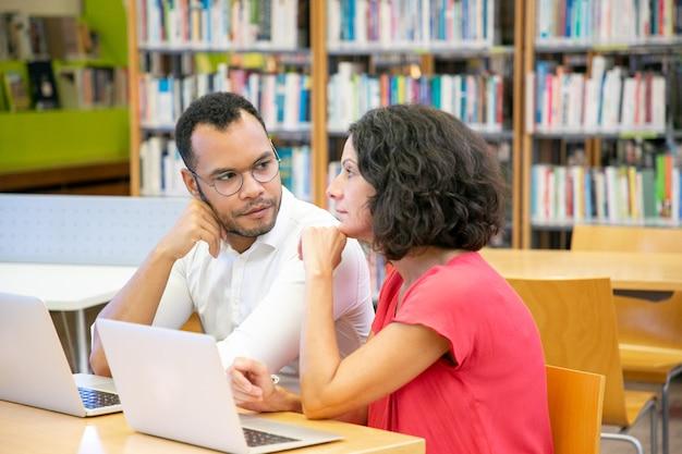 Estudiantes adultos serios mirando y discutiendo el seminario web