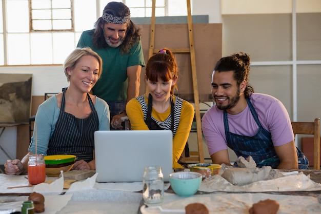 Estudiantes adultos sonrientes y enseñan mirando la computadora portátil