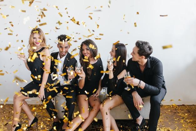 Estudiantes alegres celebrando las vacaciones con confeti y relajándose en el sofá