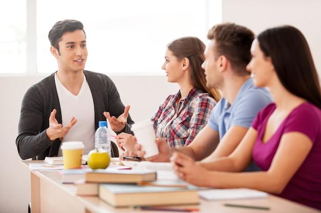 Estudiantes alegres. cuatro estudiantes alegres hablando entre sí mientras están sentados en el escritorio