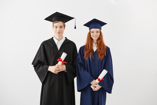 Estudiantes alegres graduados sonrientes sosteniendo diplomas.