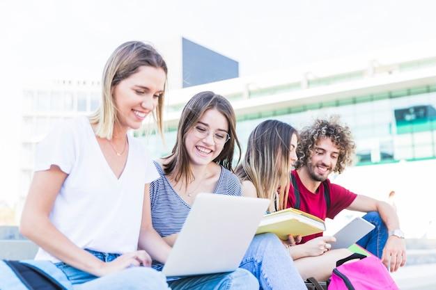 Estudiantes alegres que estudian en la calle
