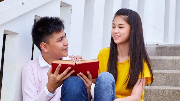 Estudiantes amigos sentados en las escaleras usando libro