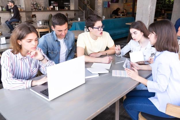 Estudiantes aprendiendo juntos en cafe