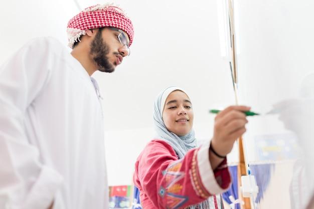 Estudiantes árabes musulmanes resolviendo una pregunta de matemáticas en la pizarra