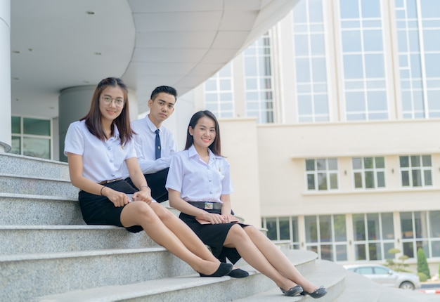 Estudiantes asiáticos felices en emplazamiento de uniforme en la universidad