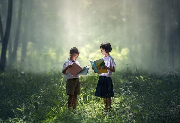 Estudiantes asiáticos leyendo libros en el campo de tailandia, tailandia, asia