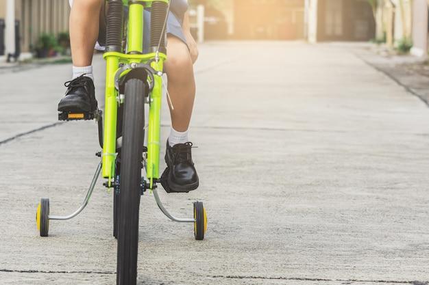 Los estudiantes asiáticos de los niños ejercitan la bicicleta al aire libre en frente del pueblo para disfrutar de un estilo de vida, un paseo feliz, andar en bicicleta, entrenar y disfrutar aprender a andar en bicicleta.
