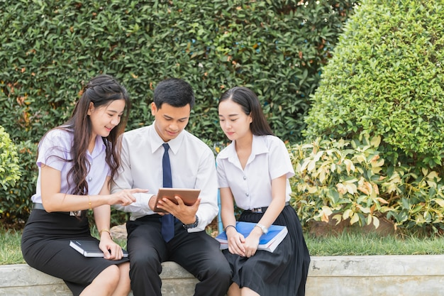 Estudiantes asiáticos usando tableta para hacer tarea
