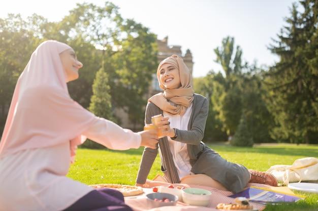 Estudiantes bebiendo refrescos. estudiantes musulmanes sonrientes bebiendo refrescos mientras almuerzan fuera cerca de la universidad