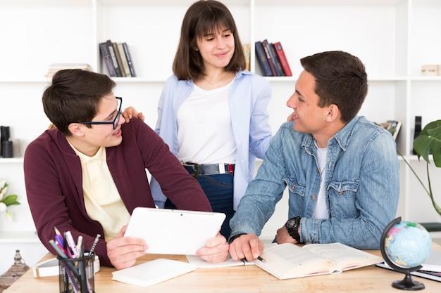 Estudiantes en biblioteca estudiando juntos