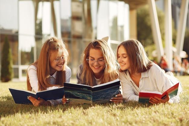 Estudiantes en el campus con libros y bolsas.
