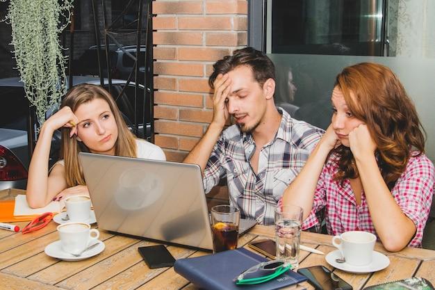 Estudiantes cansados con el ordenador portátil en café
