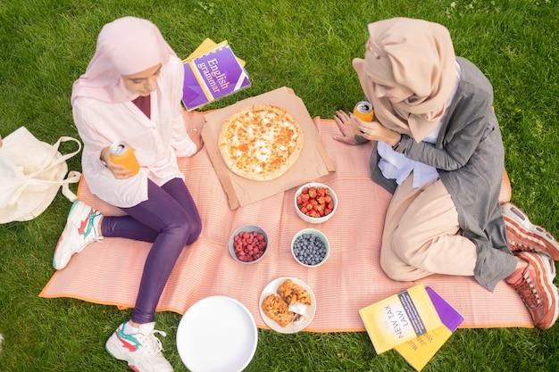 Estudiantes comiendo pizza. vista superior de estudiantes ocupados comiendo pizza y bebiendo bebidas gaseosas mientras están sentados en el césped