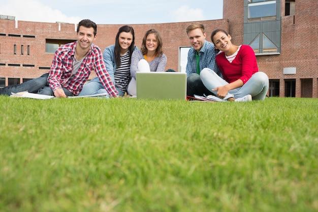 Estudiantes con la computadora portátil en el césped contra el edificio de la universidad