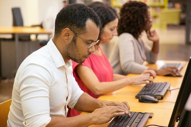 Estudiantes concentrados que trabajan con computadoras en la biblioteca