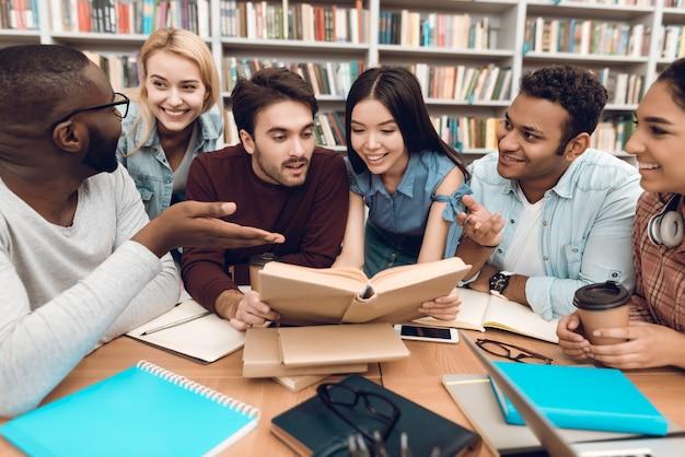 Estudiantes discutiendo estudiar en la biblioteca.
