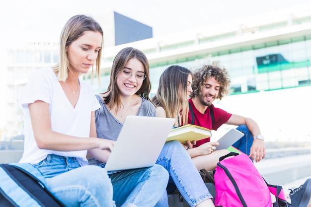 Estudiantes con dispositivos digitales en la calle