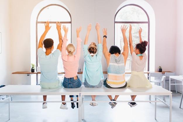 Estudiantes divertidos posando con las manos en alto para el álbum de fotos antes de graduarse. foto interior desde atrás de personas sentadas frente a una ventana grande en un apartamento de luz.